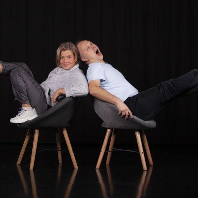 Jeanette Björkqvist och Magnus Londen sitter i två stolar i en svart miljö och spretar ut med benen åt varsitt håll. Jeanette tittar in i kameran och Magnus gäspar stort.