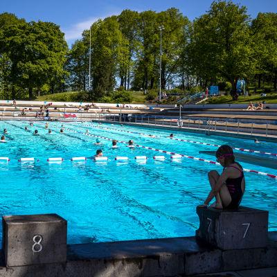 En flicka sitter på kanten till en utesimbassäng där flera människor simmar en solig dag.