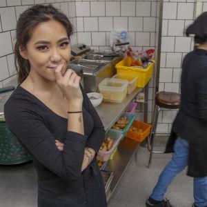 Ninni Ngueyn står i köket och ser in i kameran medan mamman Thu Nguyen arbetar.