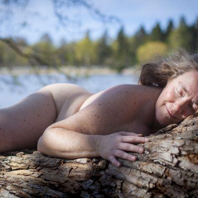 Monika Pensar naken på en trädstam.