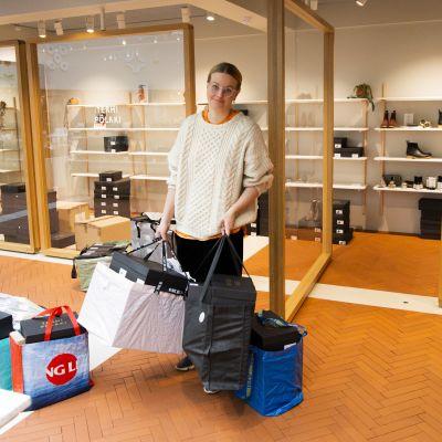 Yrittäjä  ja kenkäsuunnittelija Terhi Pölkki tyhjentää myymäläänsä Kämp Galleriassa koronaviruksen vuoksi 18. maaliskuuta 2020.
