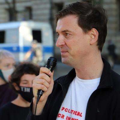 Sergej Medvedev talar i en mikrofon utanför den ryska ambassaden i Berlin