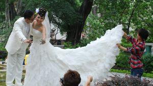 Ett brudpar från Hongkong blir fotograferade. En assistent håller upp brudklänningens släp.