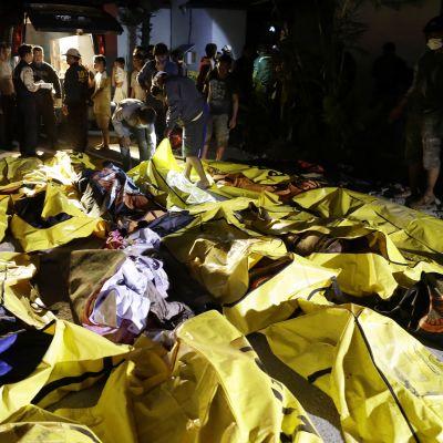 Indonesiska räddningsarbetare inspekterar dödsoffer efter tsunamin i Palu.