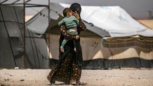 En kvinna bär på ett litet barn inne i lägret al-Hol 2.6.2019.