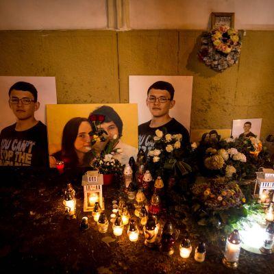 på bilden syns ljus, blommor och fotografier för att hedra journalisten Jan Kuciaks minne.