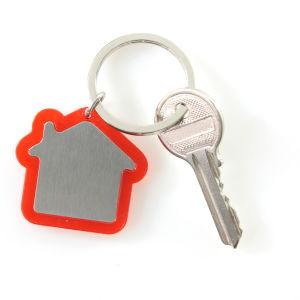 En nyckel fastsatt i en nyckelring som föreställer en stuga.