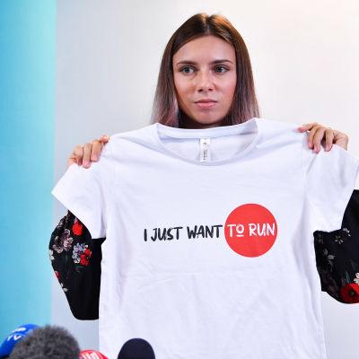 """Krystsina Tsimanouskaya näyttää T-paitaa jossa lukee """"Ijust want to run""""."""