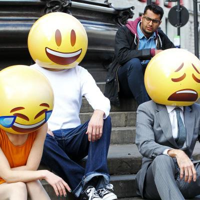 Kolme ihmistä rappusilla kasvojen kohdalla hymiöt
