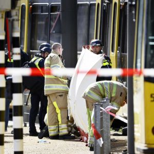 Räddningspersonal håller i ett vitt skynke framför en gul spårvagn för att skymma sikten.