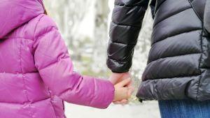 En flicka och kvinna går hand i hand. Flickan iklädd rosa jacka och kvinnan svart jacka.