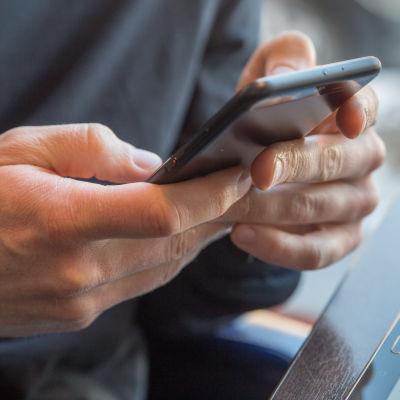 Två händer som knapprar på en svart smarttelefon. I den högra kanten syns en surfplatta.