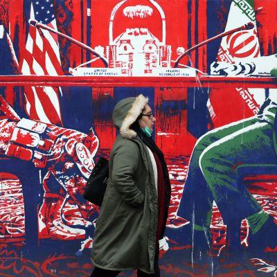 Nainen käveli amerikkalaisvastaisen seinämuraalin ohitse Iranin pääkaupungissa Teheranissa joulukuussa 2020.