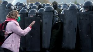 Demonstrant framför poliser under demonstration i Minsk 25.10.2020