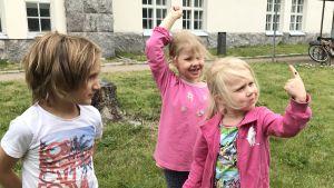 Flicka håller upp nyckelpiga på sitt pekfinger, två andra barn ser på.