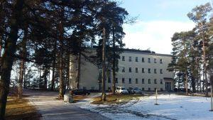 En snöig väg och snöig fotbollsplan framför en ljusgul byggnad i fyra våningar, Esperi Hoitokoti Rehabia.