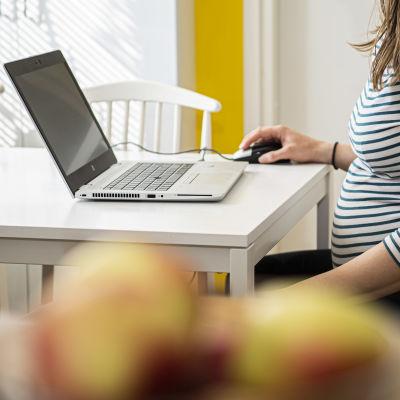 Raskaan oleva henkilö työskentelee kannettavalla tietokoneella keittiön pöydän ääressä.