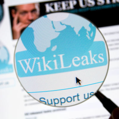 Wikileaks logo i ett förstoringsglas, i den suddiga bakgrunden Julian Assange.