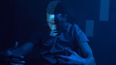 En dansare på enn mörk scen upplyst med svagt blåaktigt ljus.