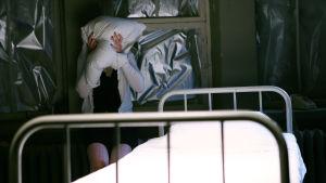 I förgrunden en sjukhussäng. Bakom den står en kvinna som pressar en vit kudde mot sitt ansikte.