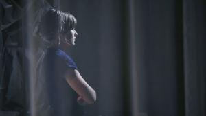 En ung kvinna står i profil mot en mörk bakgrund bakom en genomskinlig gardin.