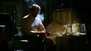 En man i ljus tröja sitter på en säng och röker.