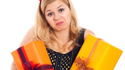 Grimaserande blond kvinna med famnen full av inslagna gåvor