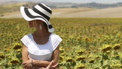 Nainen seisoo rimpsumekossa, kasvot suurilierisen hatun varjossa keskellä auringonkukkapeltoa.