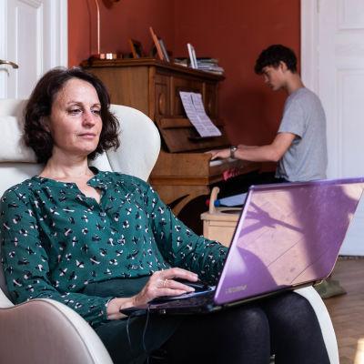 En kvinna sitter i en fåtölj och jobbar. Hon har en bärbar dator i famnen. I bakgrunden syns en yngre man som spelar piano.