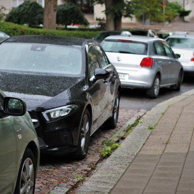 En rad med parkerade bilar, varav en är svängd åt motsatt håll.