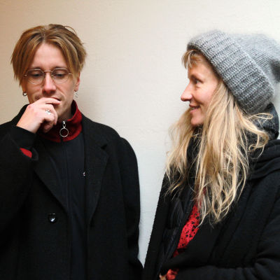Henri Tuulasjärvi mietteliäänä ja Marie Kajava hymyilevänä ulkovaatteissaan valkoista seinää vasten.