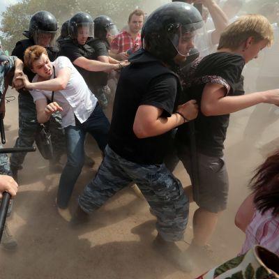 Ryska poliser knuffar en aktivist under en prideparad i S:t Petersburg 29.6.2013.