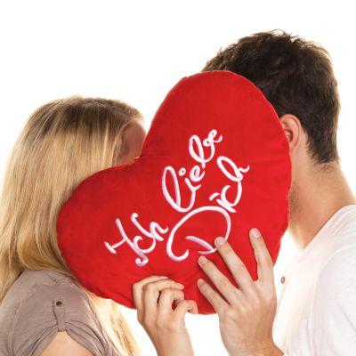 en kvinna och en man döljer sina ansikten bakom en hjärtformad kudde  där det står ich liebe dich.