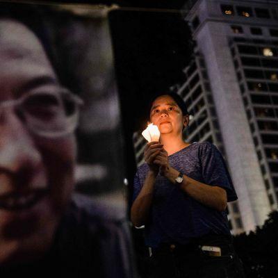 En kivnna håller ett ljus invid en stor bild av Liu Xiaobo.