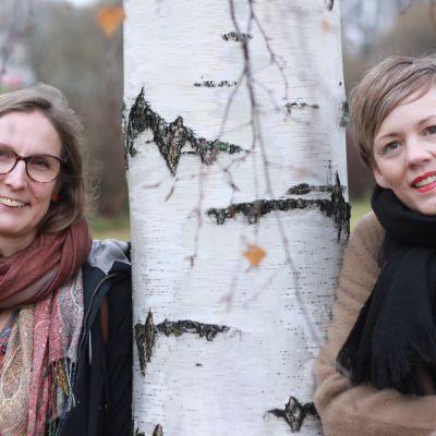 Tove Lönnqvist och Pia Sundell står och lutar mot en björk