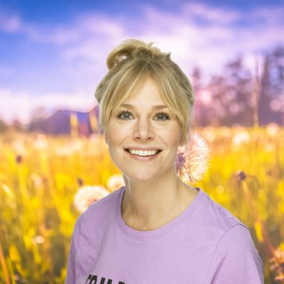 Eva Kela ler rakt in i kameran - en sommaräng syns i bakgrunden.