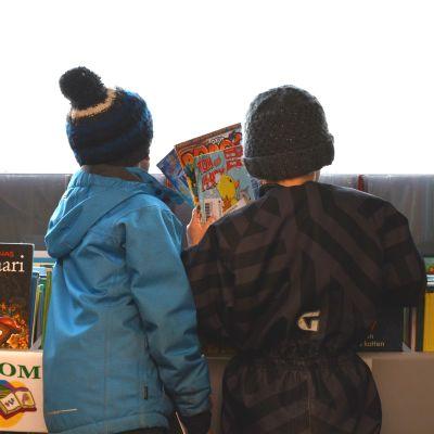 Två pojkar väljer ut serietidningar i Sibbos bokbuss.