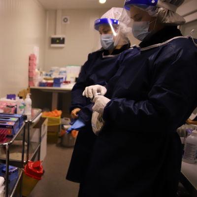 Två sjukskötare i skyddsutrustning står vid en coronatestningsstation.