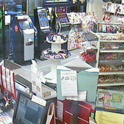 Hupulla ja aurinkolaseilla itsensä naamioinut henkilö astuu kioskiin sisään turvakamerakuvassa.