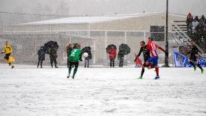 Spelarna har svårt att få kontroll över bollen på den hala planen.