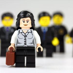 En affärskvinna som står framför en massa män iklädda kostym.
