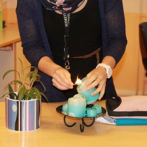 Opettaja sytyttää kynttilän