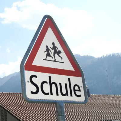 Koululaisista varoittava liikennemerkki. Taustalla vuoret.