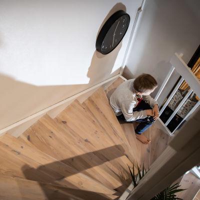 Lapsi istuu sisällä portailla.