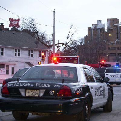 Polisbilar utanför bryggerikomplexet Molton Coors i Milwaukee på onsdag kväll. Också ovanpå den vita byggnaden till vänster görs det reklam för det kända ölmärket Miller.