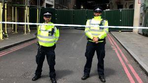 Londonpoliser står vakt utanför ingången till Borough Market, där flera människor höggs ihjäl i terrorattacken den 3 juni 2017.