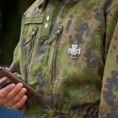En militärklädd person med smarttelefon i handen.