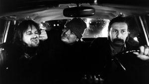 Mustavalkoinen kuva, jossa taksinkuljettaja ja kaksi humalaista miestä