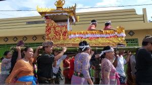 begravningsceremoni i Bali. En färggrant prydd kista bärs på närmare tio personers axlar genom byns gata.