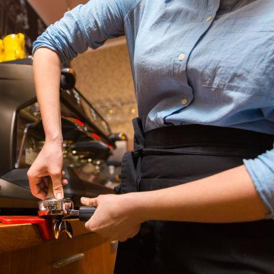 Servitris färdigställer kaffe.